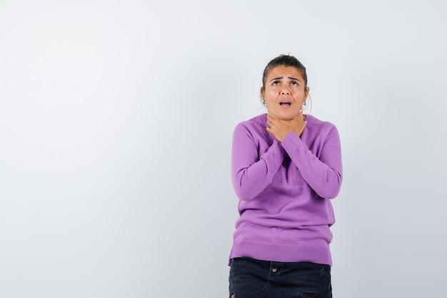 Kobieta w wełnianej bluzce cierpi na ból gardła i wygląda na chorą