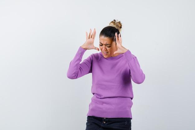 Kobieta w wełnianej bluzce podnosi ręce, krzycząc i wyglądając na zirytowaną