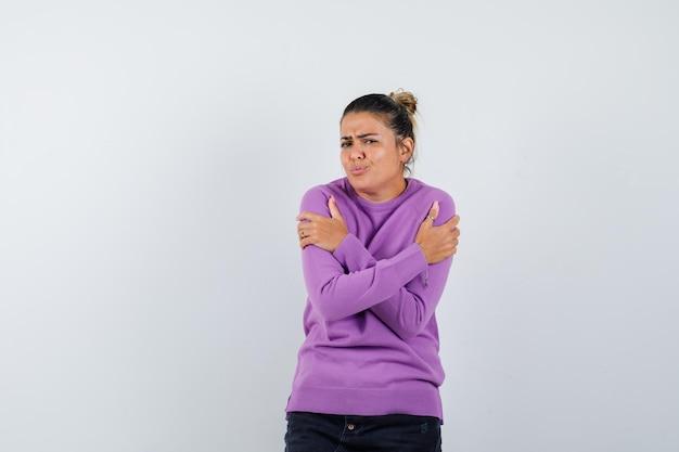 Kobieta w wełnianej bluzce przytula się lub czuje zimno i wygląda na bezradną
