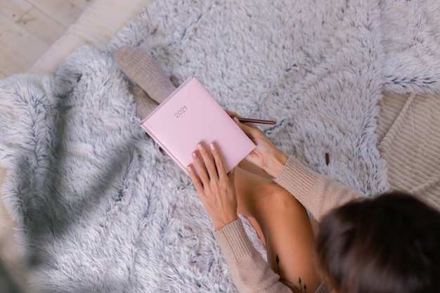 Kobieta w wełnianej skarpecie i swetrze z różowym napisem na zeszyt 2021, duży tatuaż na biodrze. kobieta siedzi na łóżku w domu w sypialni.