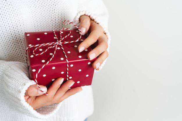 Kobieta w wełnianym białym swetrze trzymająca pudełko z kokardą. świąteczny układ świąteczny. makieta na nowy rok.
