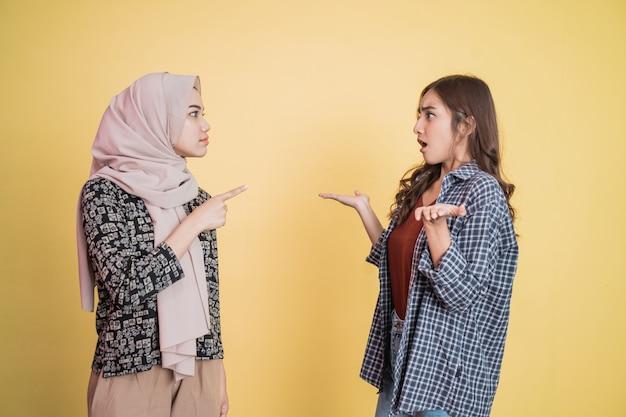 Kobieta w welonie wskazuje palcem na kobietę w geście wymijającym, gdy zostaje oskarżona