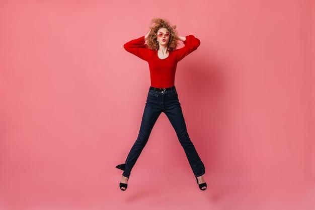 Kobieta w wesołym nastroju skacze po różowej przestrzeni. pani w okularach, czerwonej bluzce i spodniach, gwiżdżąca i dotykająca kręconych włosów.
