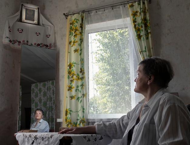 Kobieta w wiejskim retrostylowanym wnętrzu, patrząca na religijną ikonę jezusa i modlącą się na zdjęciu prawdziwych ludzi people