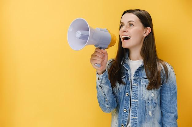 Kobieta w wieku 20 lat krzycząca w megafonie, zaciskająca pięść