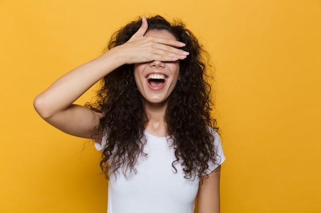 Kobieta w wieku 20 lat z kręconymi włosami, uśmiechnięta i stożkowata oczy z dłonią odizolowaną na żółto