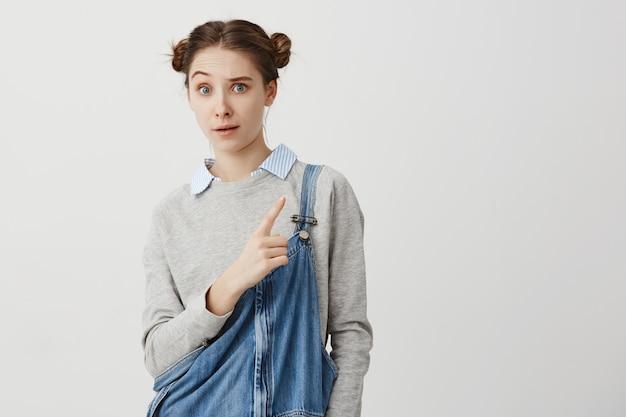 Kobieta w wieku 20 lat zastanawia się, co widzi, pokazując palec wskazujący bokiem unoszącą brew. dziewczyna z modną fryzurą odango podejrzanie pokazuje na białej ścianie. skopiuj miejsce