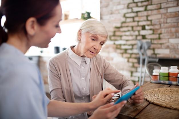 Kobieta w wieku czuje się zaangażowana w używanie tabletu z opiekunem