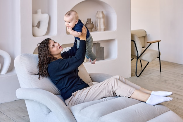 Kobieta w wieku lat z dzieckiem w rękach siedzi w salonie
