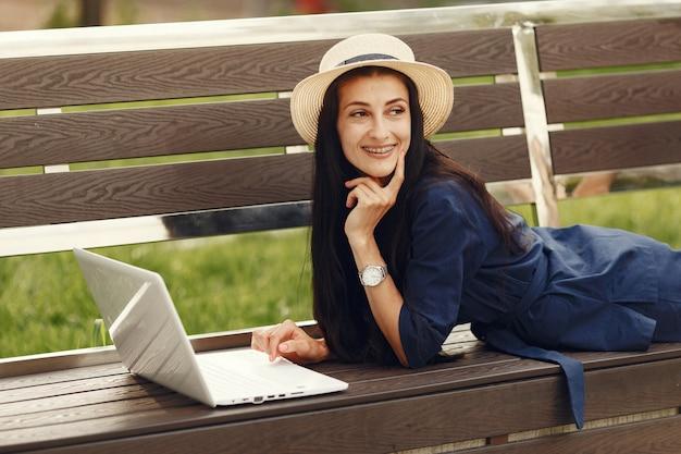 Kobieta w wiosennym mieście. pani z laptopem. dziewczyna siedzi na ławce.