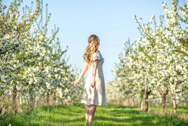 Kobieta w wiśniowym kwitnącym sadzie na wiosnę