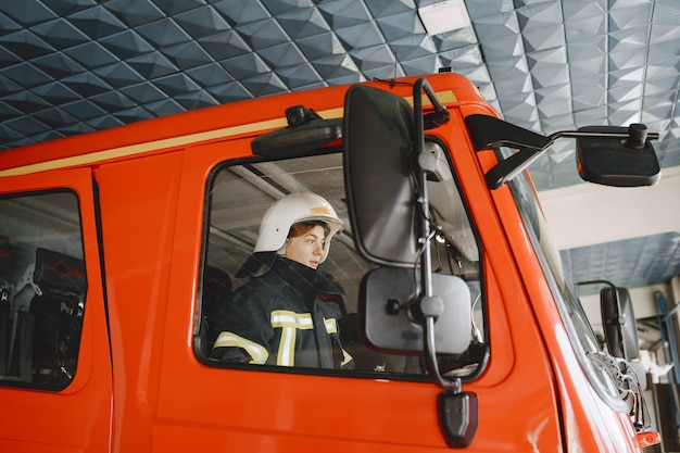 Kobieta w wozie strażackim. czerwony wóz strażacki. strażacy zamykają drzwi samochodu.
