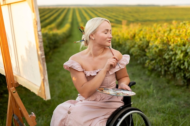 Kobieta w wózku inwalidzkim malowanie na zewnątrz