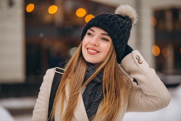 Kobieta w żakiet pozyci na zewnątrz kawiarni w zimy ulicie