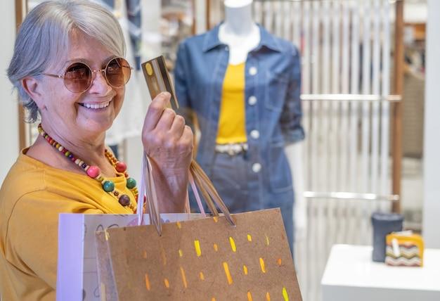 Kobieta w zakupach. uśmiechnięta starsza pani z kartą kredytową w dłoni przed sklepem, pojęcie konsumpcjonizmu.