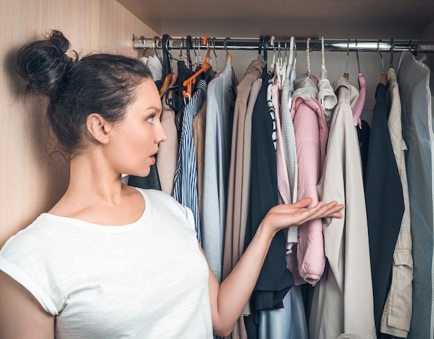 Kobieta w zamyśleniu patrzy na wiszące w szafie rzeczy.