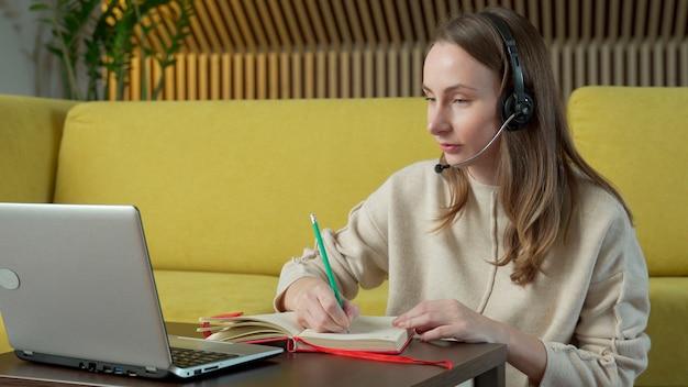 Kobieta w zestawie słuchawkowym siedzi na żółtej kanapie w domu i rozmowy wideo na komputerze przenośnym.