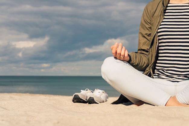Kobieta w zielonej kurtce i dżinsach siedzi boso na plaży i medytuje