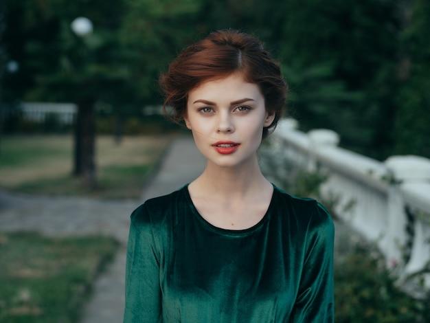 Kobieta w zielonej sukience czerwone usta romans park spacer