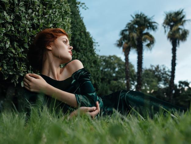 Kobieta w zielonej sukience leży na trawie bajki ogród natura