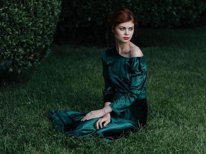 Kobieta w zielonej sukience leży na trawie pozując glamour maskarada ogród