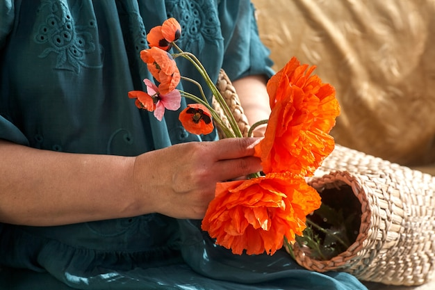 Kobieta w zielonej sukience trzymająca kwiaty maku z bliska na dłoniach wiosenne sny