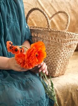 Kobieta w zielonej sukni trzyma kwiaty poppe, z bliska na jej rękach. wiosenne sny.
