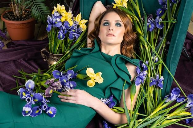 Kobieta W Zielonej Sukni Z Kwiatami Premium Zdjęcia