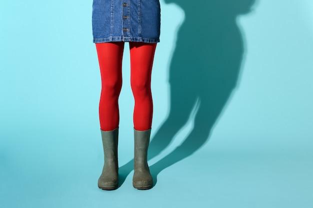 Kobieta w zielonych kaloszach na sobie krótką spódniczkę dżinsową i czerwone rajstopy