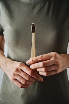 Kobieta w zielonym krótkim t-shircie trzyma bambusową szczoteczkę do zębów