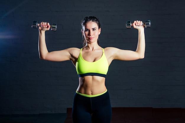 Kobieta w zielonym sportowym staniku i czarnych spodniach ćwicząca na siłowni i podnosząca hantle na tle czarnych cegieł