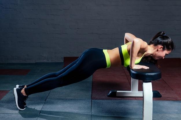 Kobieta w zielonym sportowym staniku i czarnych spodniach potrząsa prasą na ławce na tle czarnych cegieł