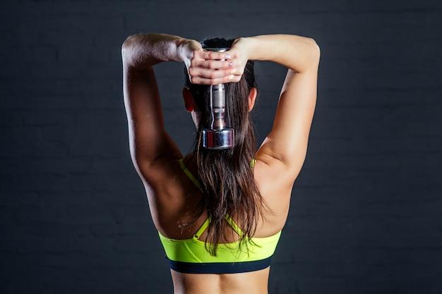 Kobieta w zielonym sportowym staniku uprawiająca siłownię z hantlami na tle czarnych cegieł