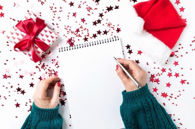 Kobieta w zielonym swetrze pisze listę kontrolną planów i marzeń na przyszły rok. lista życzeń na boże narodzenie i nowy rok. lista rzeczy do zrobienia na nowy 2020 rok z czerwonym wystrojem świątecznym.