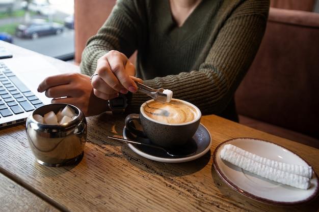 Kobieta w zielonym swetrze szczypcami dodaje kawałek cukru do swojego cappucino podczas pracy w kawiarni.