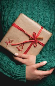 Kobieta w zielonym swetrze trzyma świąteczny prezent z czerwoną wstążką