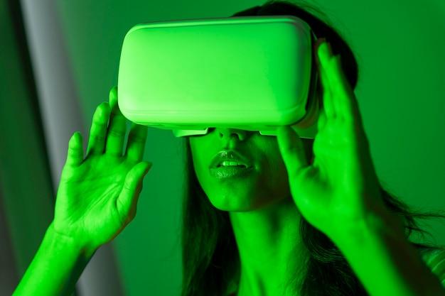 Kobieta w zielonym świetle za pomocą zestawu słuchawkowego wirtualnej rzeczywistości