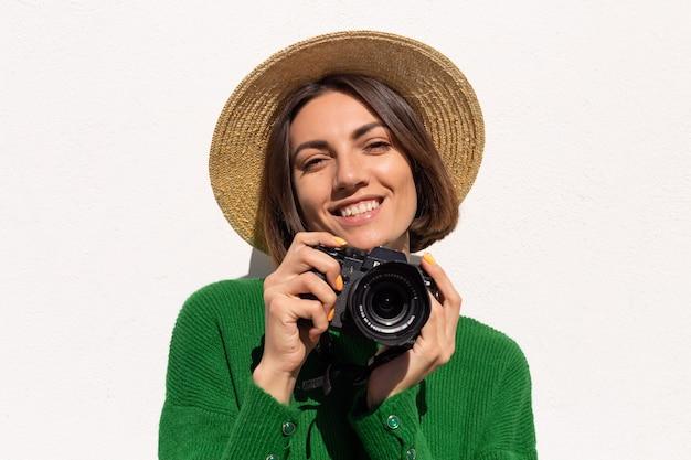 Kobieta w zielonym swobodnym swetrze i kapeluszu na zewnątrz na białej ścianie szczęśliwy pozytywny turysta z profesjonalnym aparatem