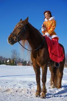 Kobieta w zimie na koniu w słoneczny mroźny dzień