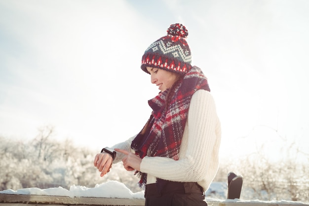 Kobieta w zimie nosić sprawdzanie jej smartwatch