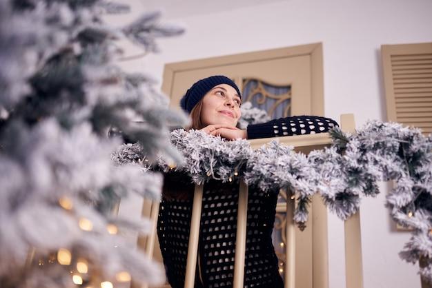Kobieta w zimie w pobliżu okna w domu z zewnątrz w tle.