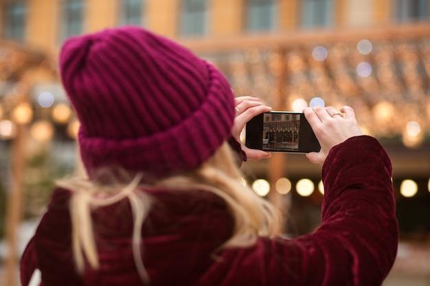 Kobieta w zimowej odzieży robi zdjęcie na smartfonie z tłem bokeh w mieście