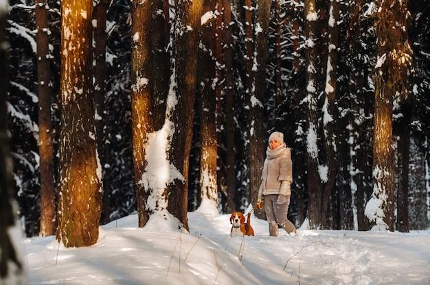 Kobieta w zimowy dzień z psem rasy beagle w zimowym lesie gra.