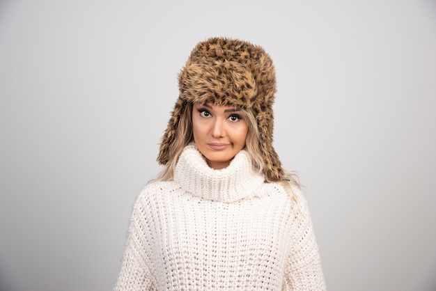 Kobieta w zimowym kapeluszu patrząc na kamery.