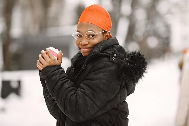 Kobieta w zimowym miasteczku. dziewczyna w czarnej kurtce. afrykańska kobieta z kawą.