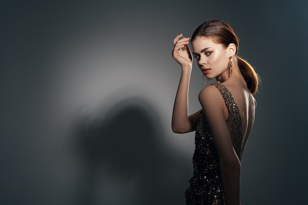 Kobieta w złotej sukience pozuje studio mody biżuterii
