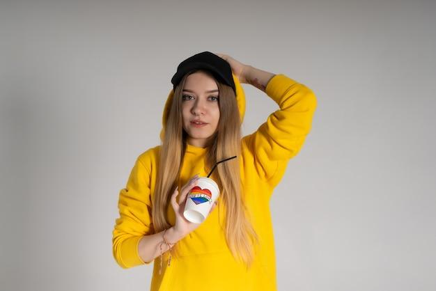 Kobieta w żółtej bluzie, czarnej czapce z przekłutym nosem, trzyma papierowy kubek z napisem love is love i tęczowym lgbtq w kształcie serca