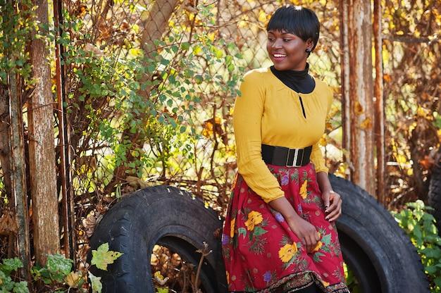 Kobieta w żółtej i czerwonej sukience w złotym parku jesień jesień