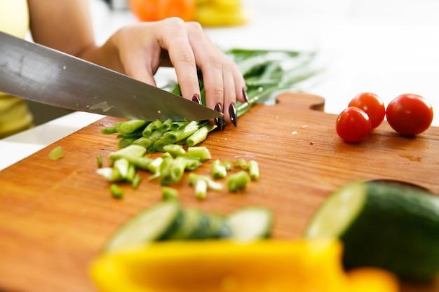 Kobieta w żółtej koszuli kawałki zielonej cebuli w kuchni