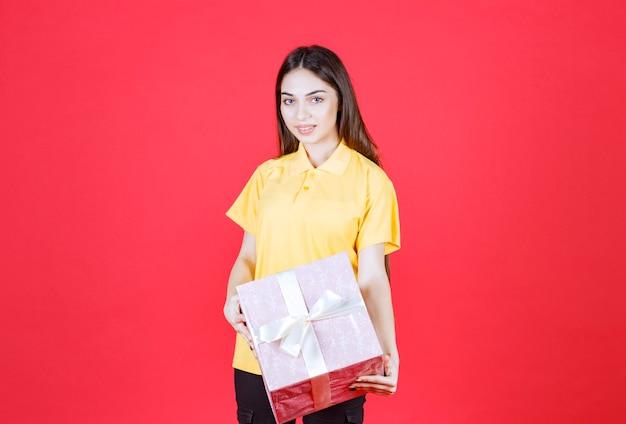 Kobieta w żółtej koszuli trzyma różowe pudełko.